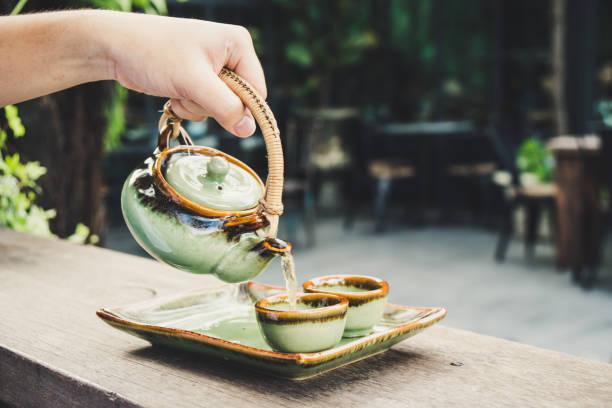 tee von teekanne asiatischen stil gießen - keramikteekannen stock-fotos und bilder