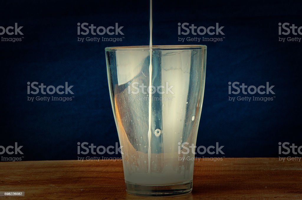 Poured milk on wooden background foto royalty-free