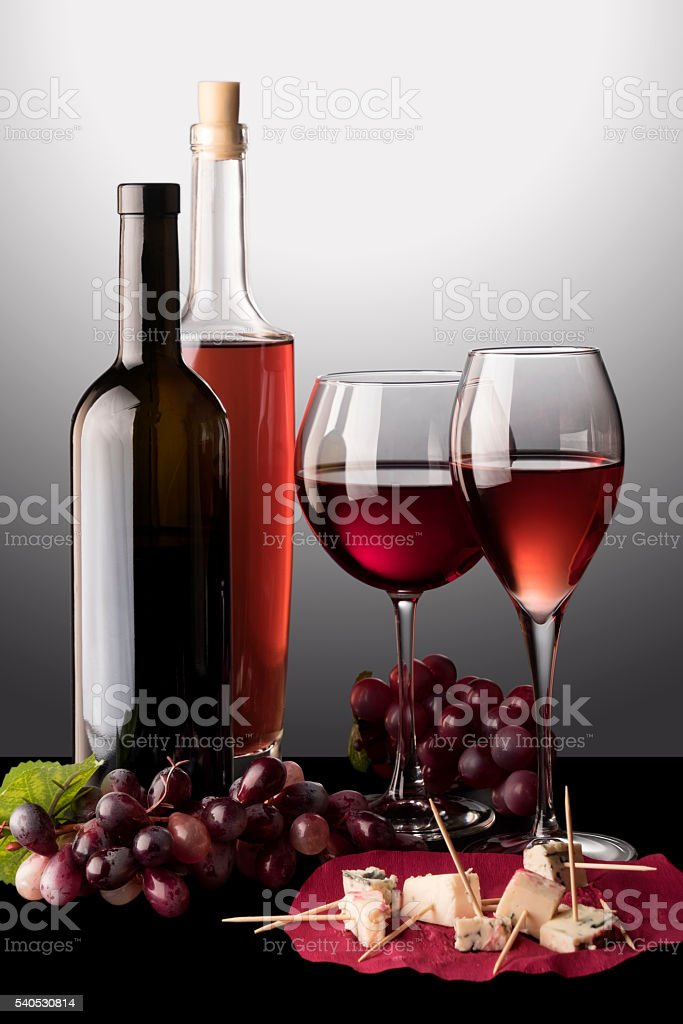 Poured wine glasses and bottles stock photo