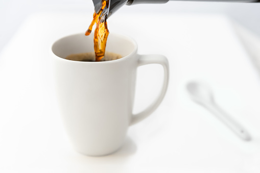 Pouring a cup of coffee on a white table.