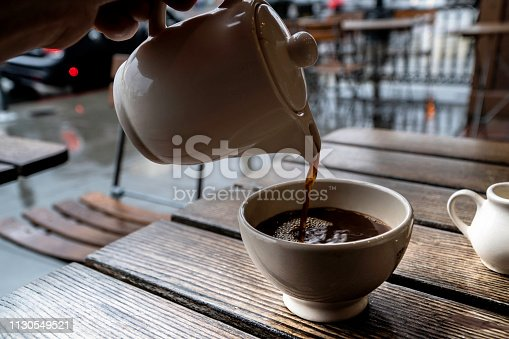 Close up of had pouring a cup of coffee in a cozy cafe.