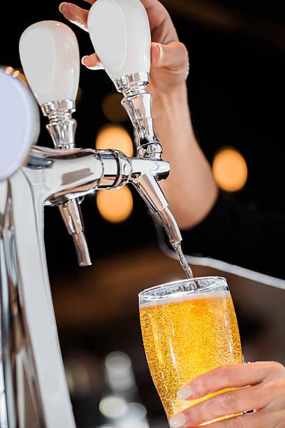 eingießen einen entwurf blonde bier vom fass - goldene bar stock-fotos und bilder