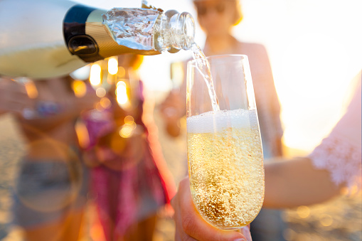 Pouring a glass of champagne with people partying in the background. The party is on the beach at sunset. Close up