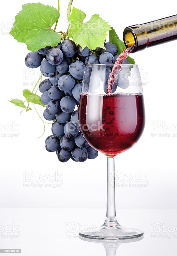 Pouring a glass of red wine and bunch grapes isolated royalty-free stock photo