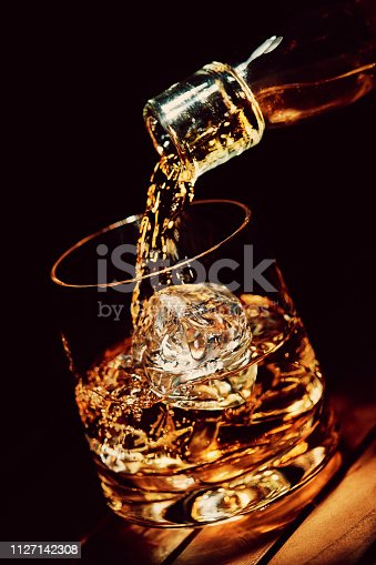 Pouring a glass of whisky with ice, in a dark background.