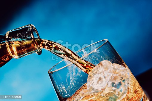 Pouring a glass of whisky with ice, in a blue background.
