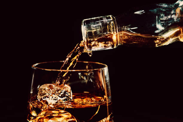 Pouring a glass of whiskey on ice stock photo