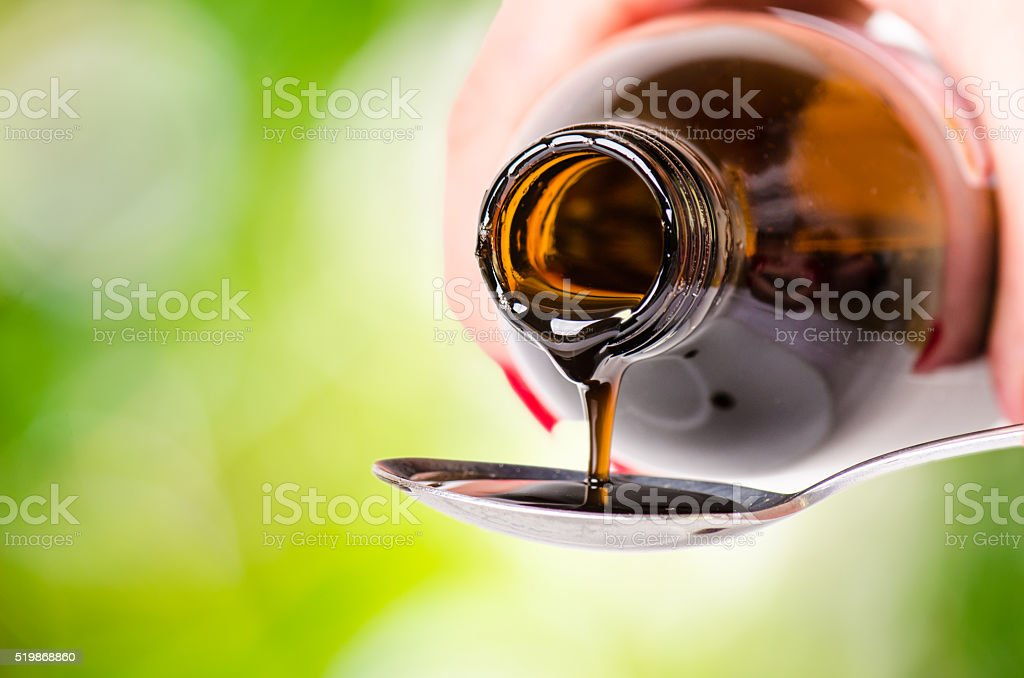 pouring a liquid on a spoon. Natural green background. stock photo