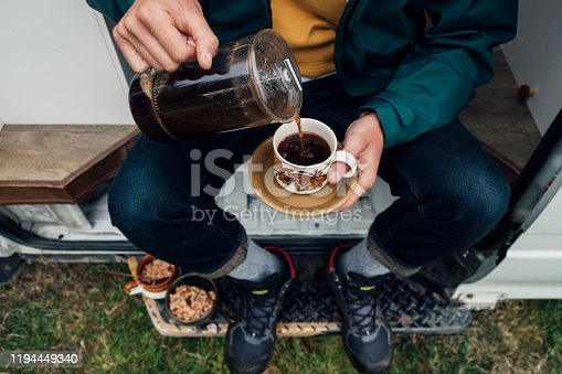 A directly above shot of a young man sitting on the side of his motor home pouring a cup of coffee.