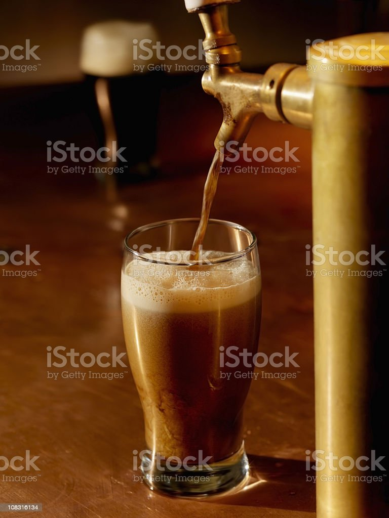 Pouring a Pint of Stout stock photo
