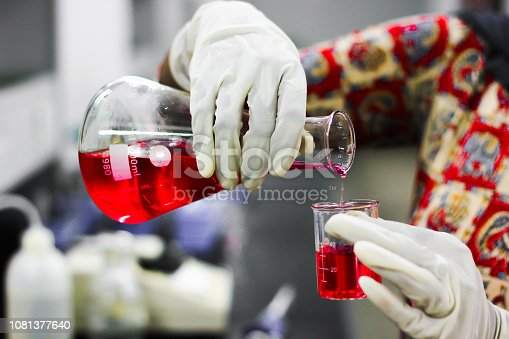 istock pouring a red liquid from a glass conical flask to a glass beaker with a gloved hand in a chemistry lab 1081377640