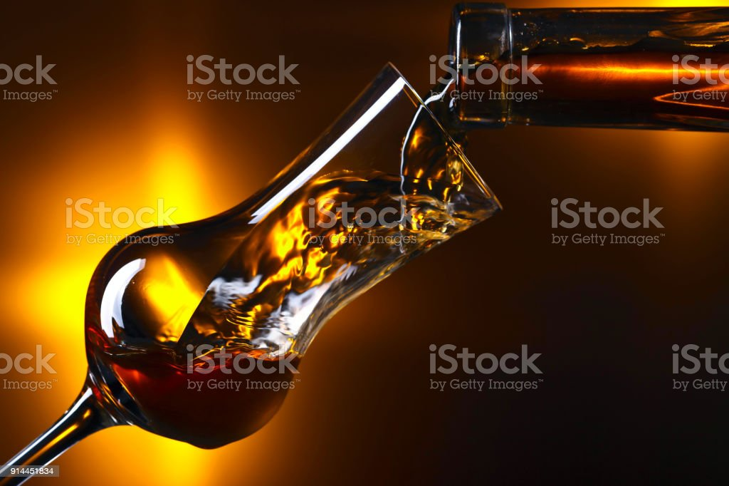 Pouring alcohol drink into a wineglass . stock photo