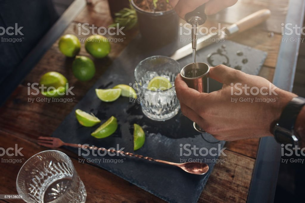 Pouring alcohol in jigger to prepare a cocktail stock photo