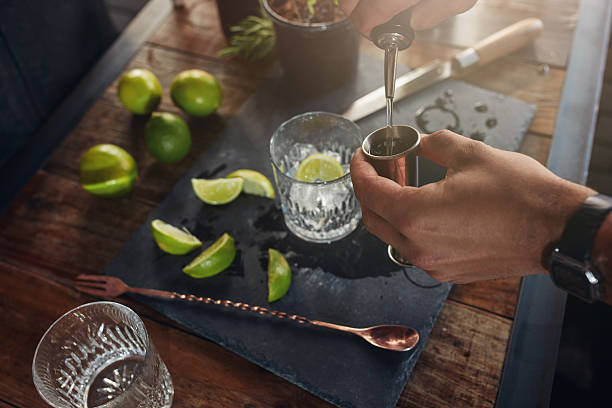Pouring alcohol in jigger to prepare a cocktail Closeup of man hands pouring alcoholic drink in to a jigger to prepare a cocktail. Barman preparing the cocktail at  the bar counter. dry measure stock pictures, royalty-free photos & images
