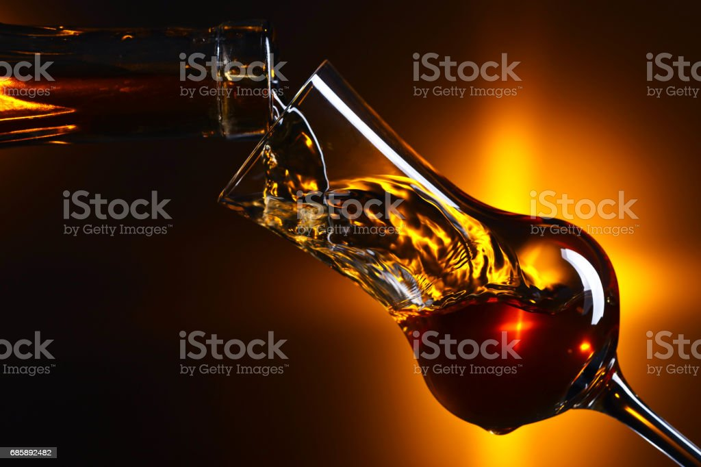 Pouring alcohol into a glass on dark background stock photo