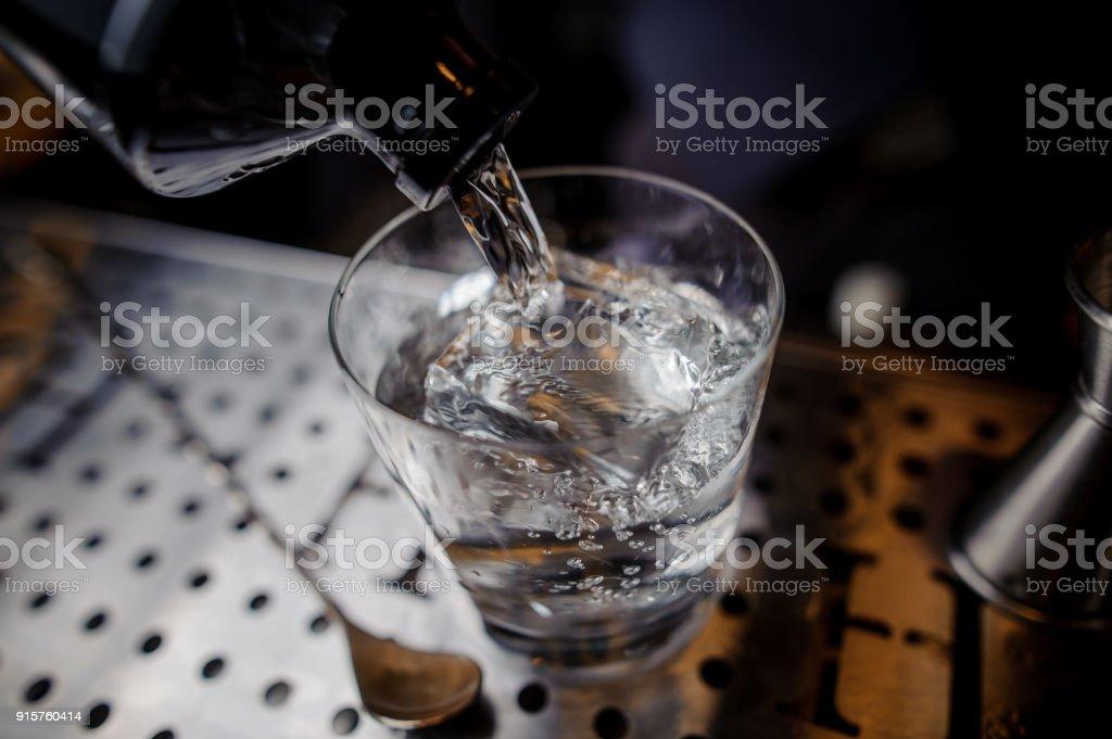 Alkoholisches Getränk in ein Glas gießen, auf dem Hintergrund der Theke – Foto