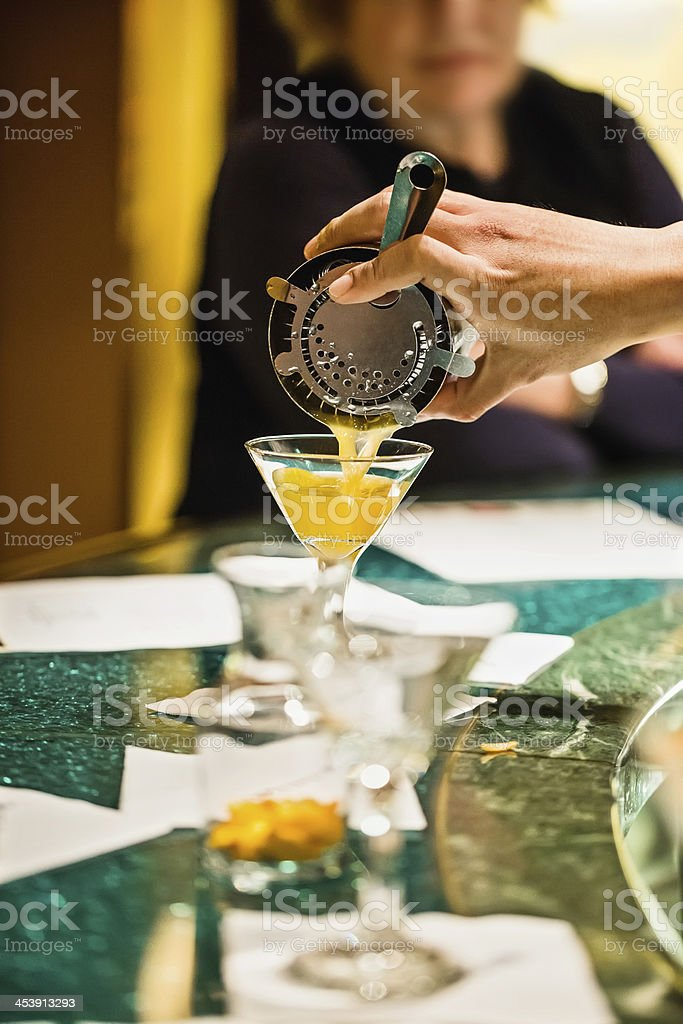 Pouring alcoholic drink into martini glass on New year's eve royalty-free stock photo