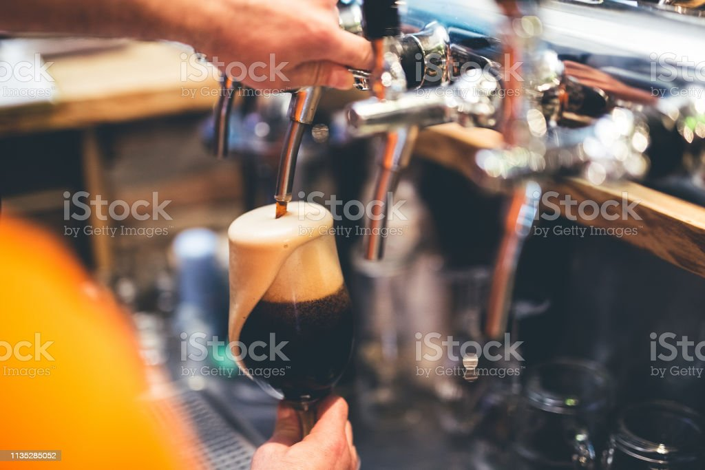 Pouring ale from a beer tap stock photo