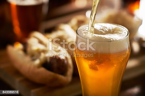 istock pouring amber beer into mug with bratwursts in background 843389516