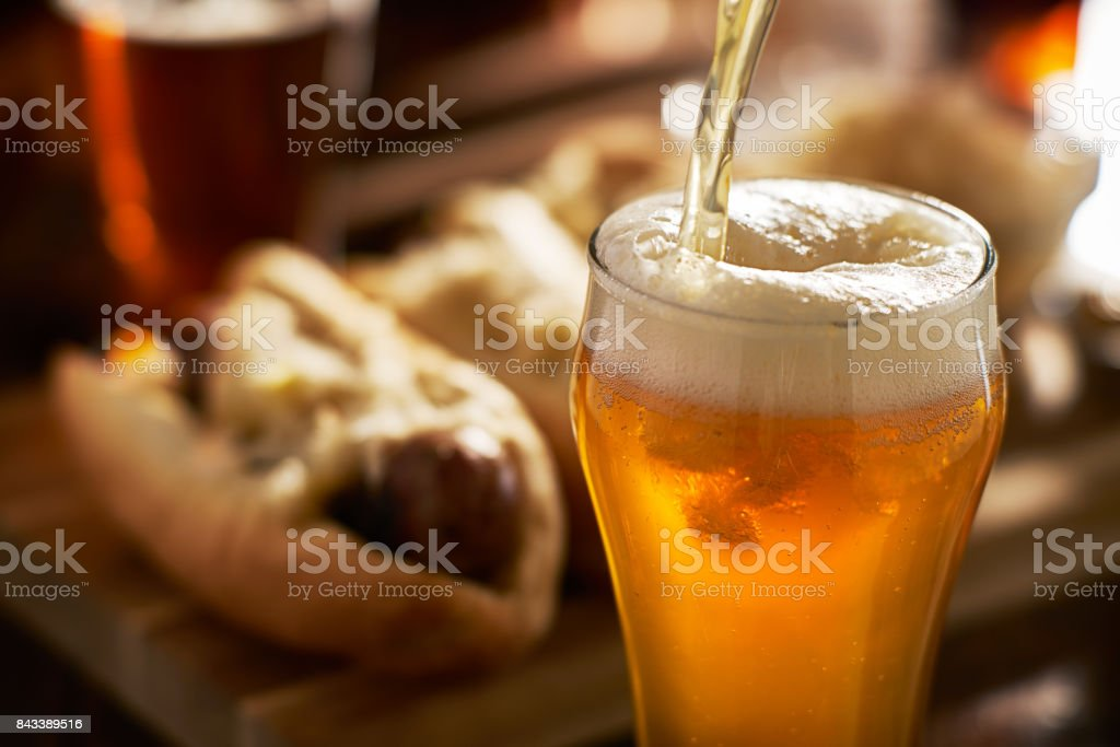 pouring amber beer into mug with bratwursts in background - fotografia de stock