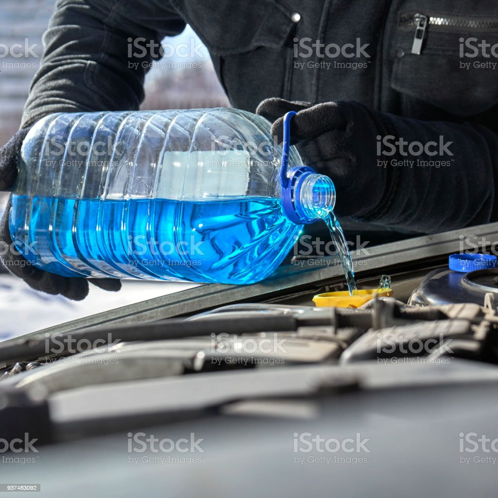 Pouring an antifreeze liquid in a windshield washer tank of a car close up stock photo