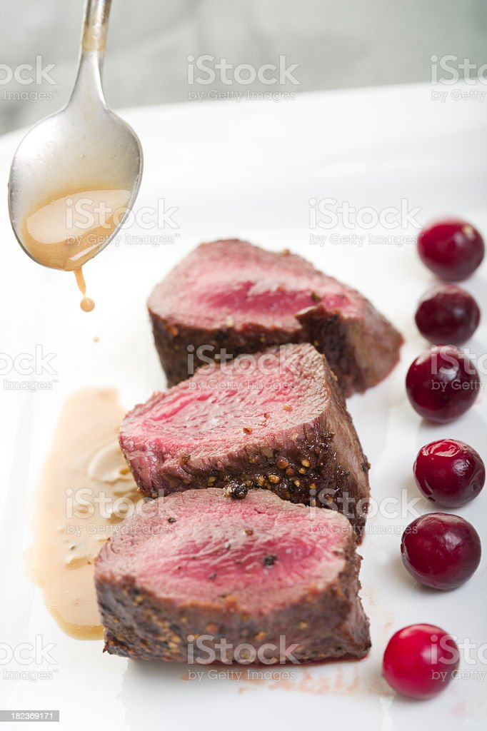 Pouring au jus on a plate of venison steaks stock photo