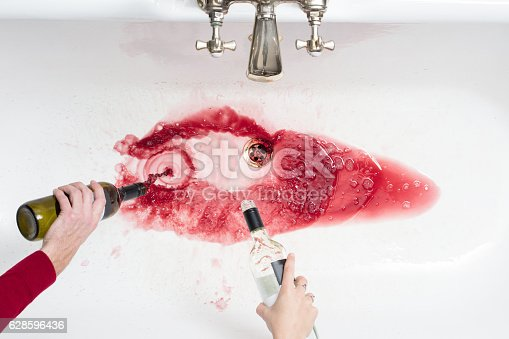istock Pouring away wine in an act of giving up alcohol 628596436