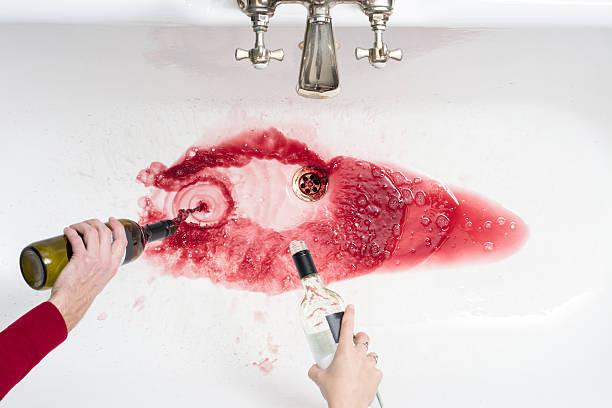 pouring away wine in an act of giving up alcohol - ausscheiden stock-fotos und bilder