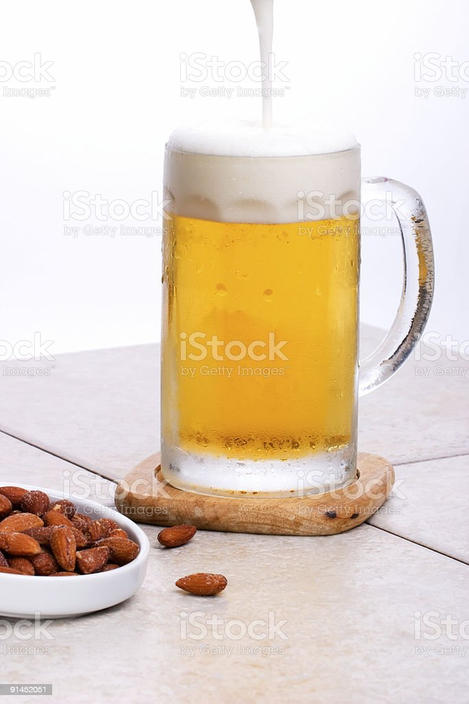 Pouring beer and nutes royalty-free stock photo