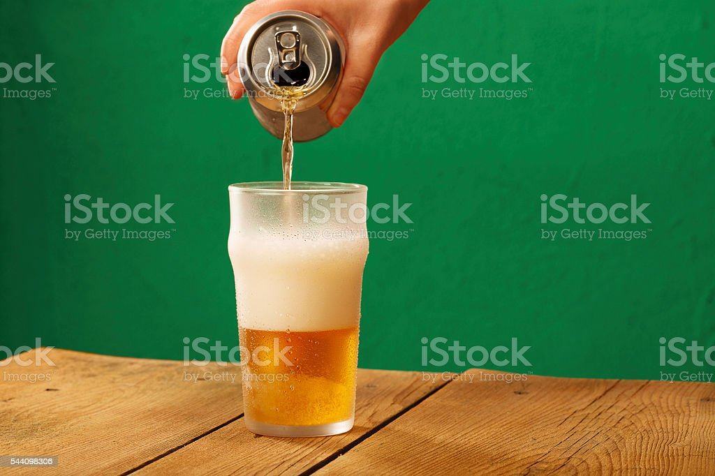 Pouring beer from can  to  ice  gllass  covered with  condensation stock photo
