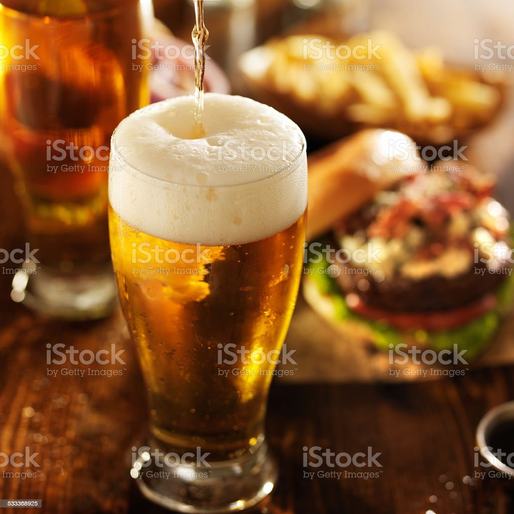 pouring beer in table with burgers stock photo