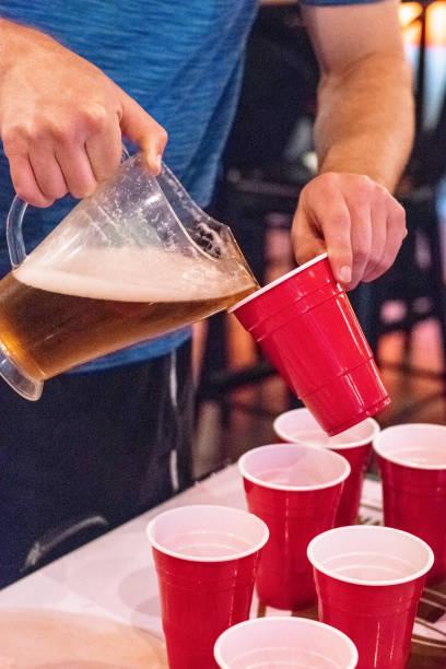 bier in tassen auf party gießen - lustige trinkspiele stock-fotos und bilder