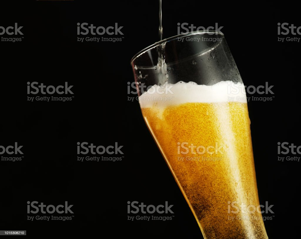 Pouring beer into glass over black background. стоковое фото