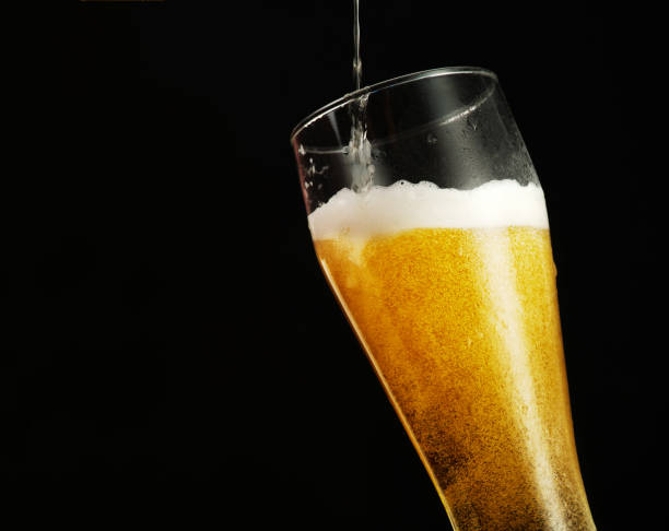 Cтоковое фото Pouring beer into glass over black background.