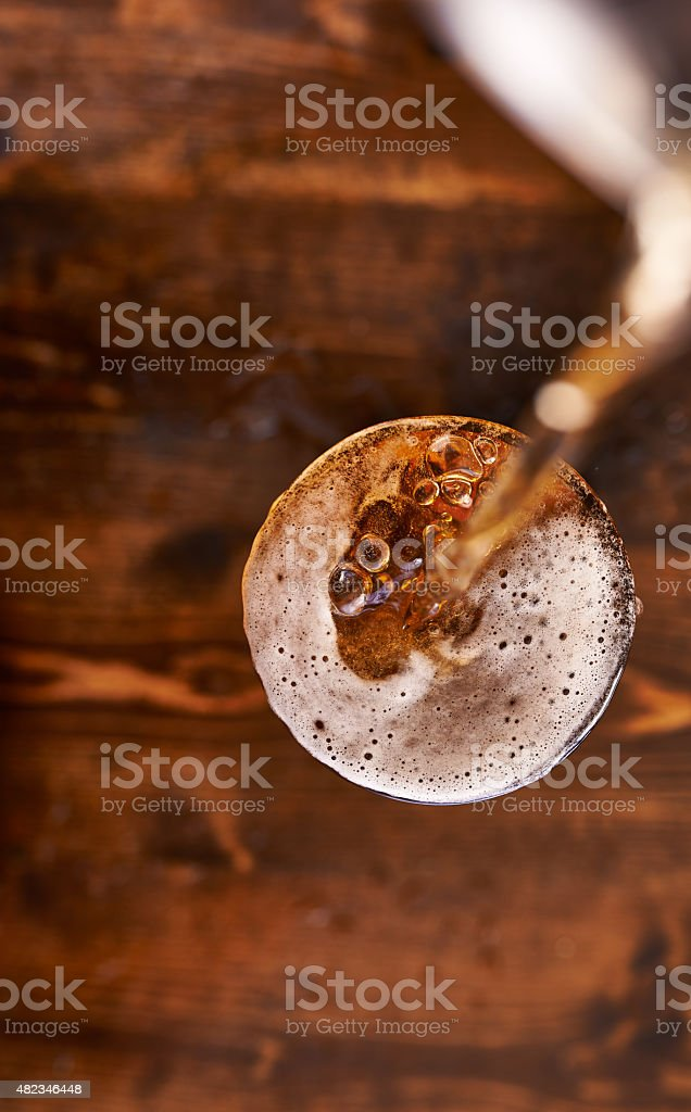 pouring beer into glass top down stock photo