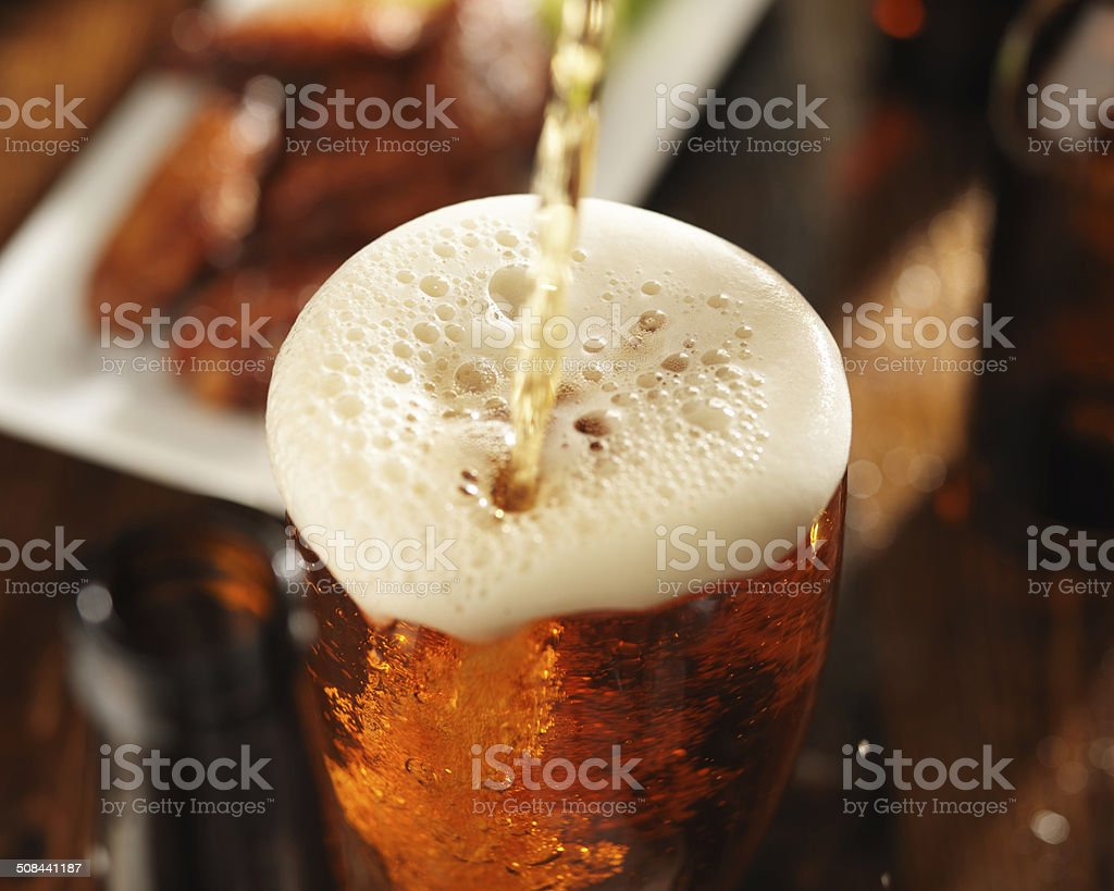 pouring beer into glass with foam stock photo