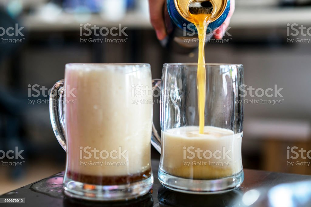 pouring beer into mug stock photo