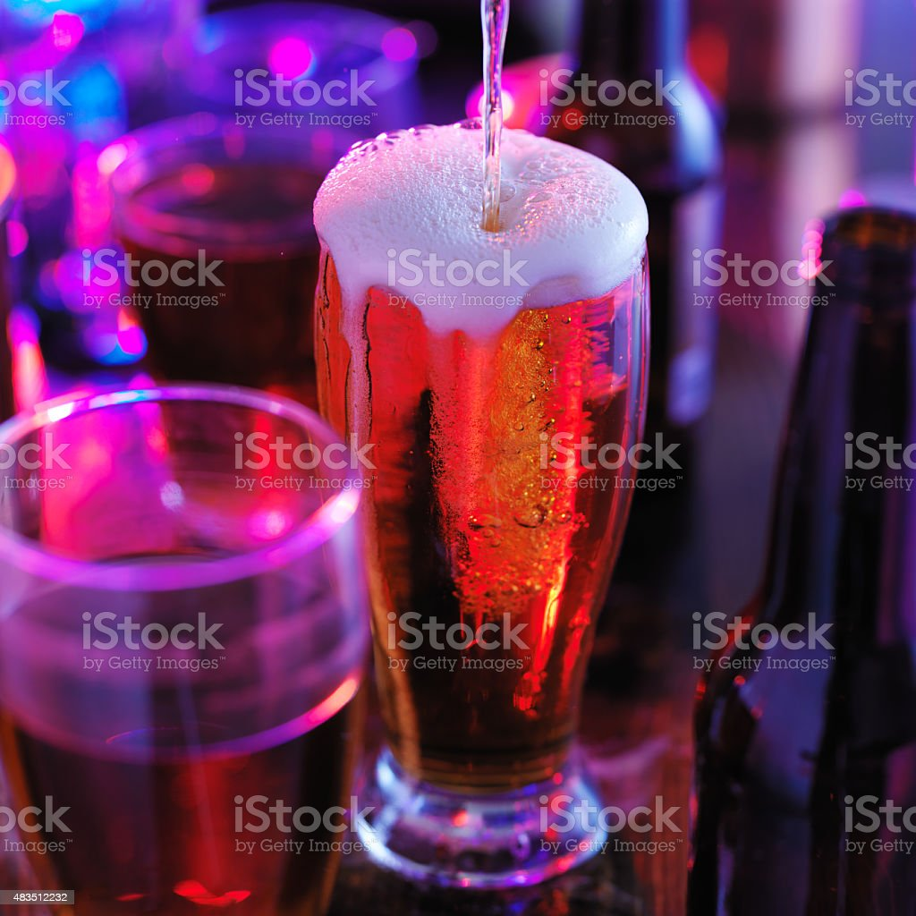 pouring beer into overflowing glass stock photo