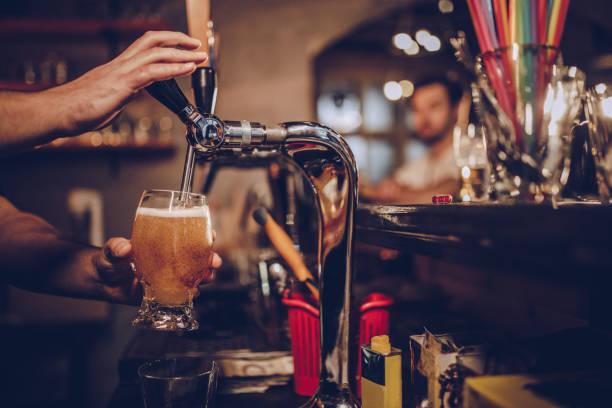 Pouring beer Man in pub pouring beer. pilsner stock pictures, royalty-free photos & images