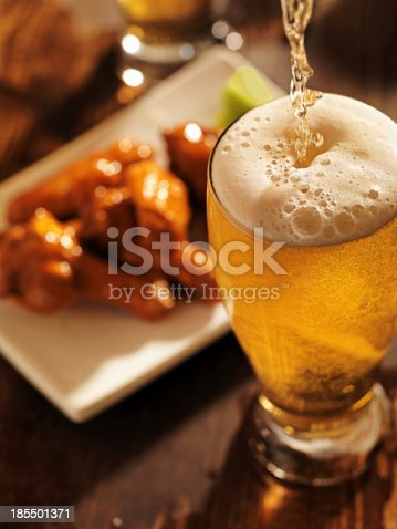 istock pouring beer with chicken wings in background. 185501371