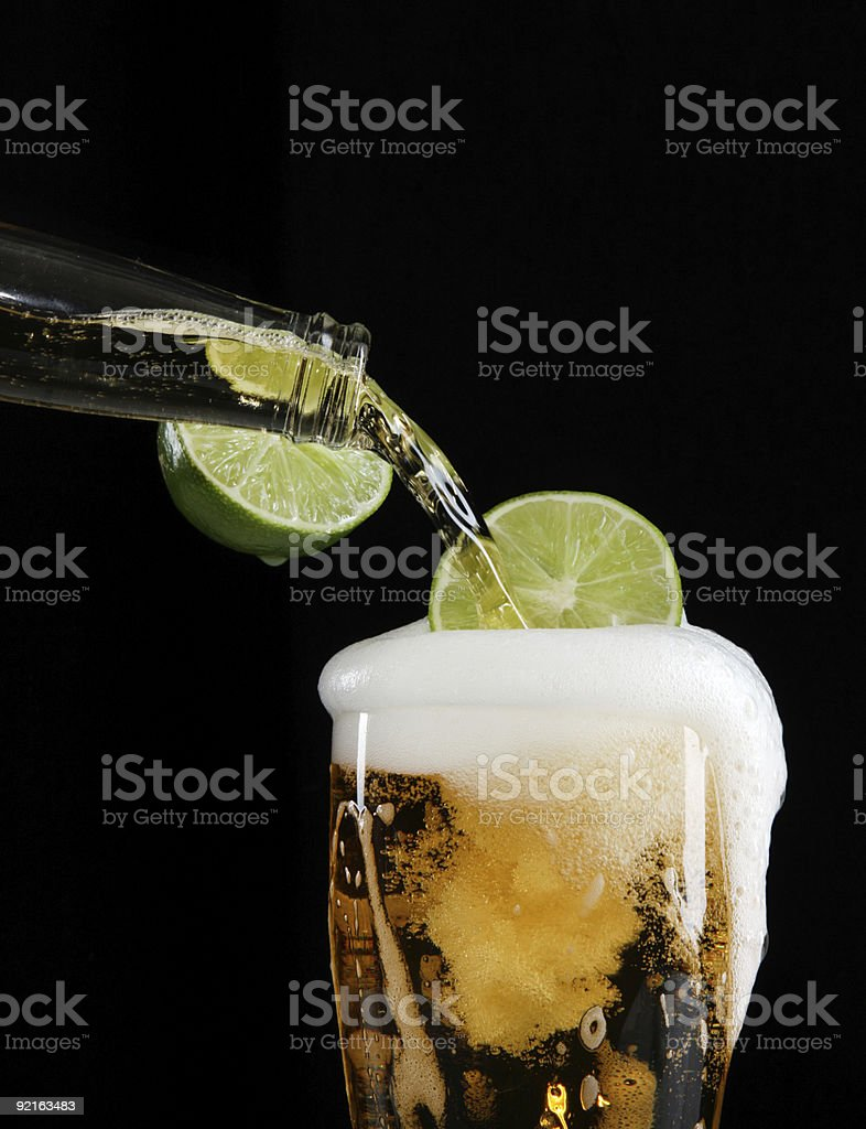 Pouring beer with lime stock photo