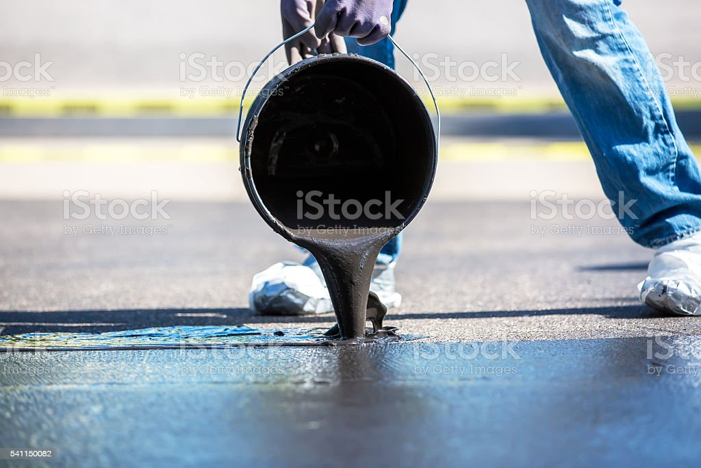 Pouring Black Tar Seal Coating Onto Driveway stock photo