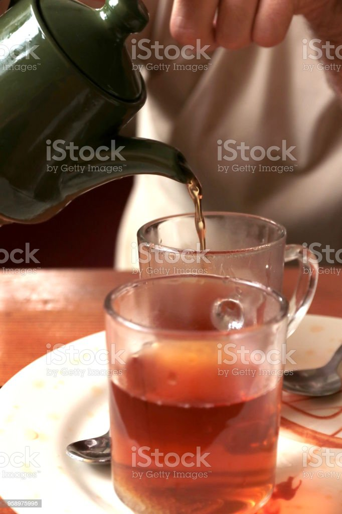 Pouring Black Tea into a Cup stock photo