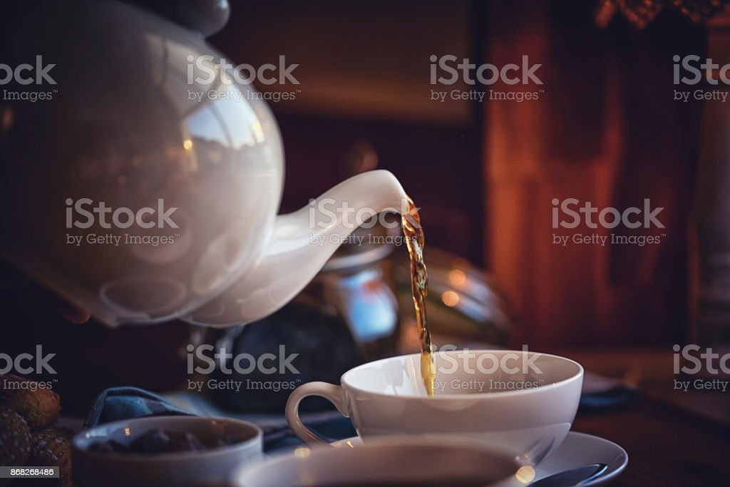 Pouring Black Tea into Cup - foto stock