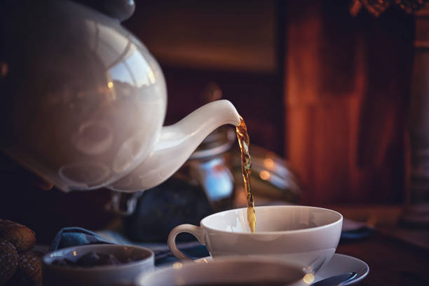 pouring black tea into cup - tea hot drink stock photos and pictures