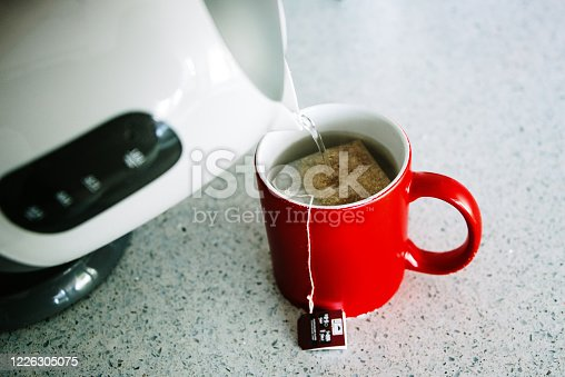 Pouring building water from an electric kettle into a red tea cup