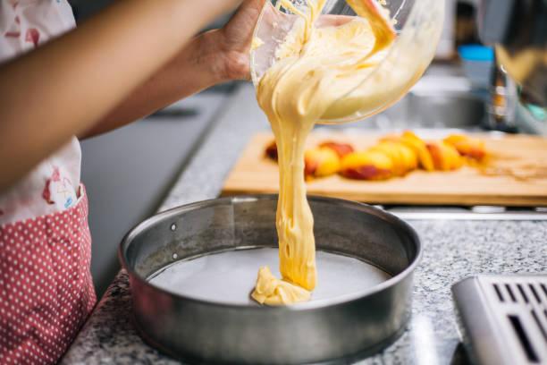 pouring cake batter into baking tin - impasto per il pane foto e immagini stock