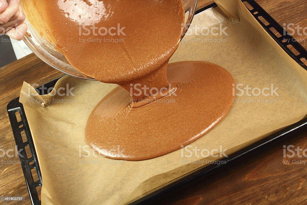 Pouring cake batter onto baking sheet stock photo