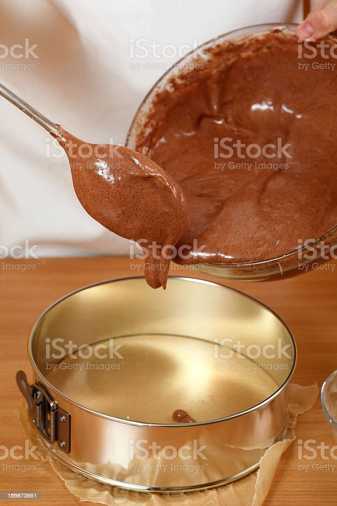 Pouring cake mix into baking tin royalty-free stock photo