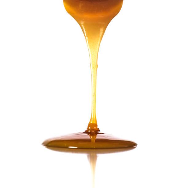 pouring caramel sauce on white background - xarope imagens e fotografias de stock